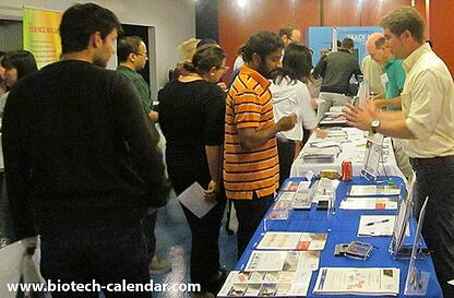 Lab supply company representative discussing laboratory research equipment with event attendees