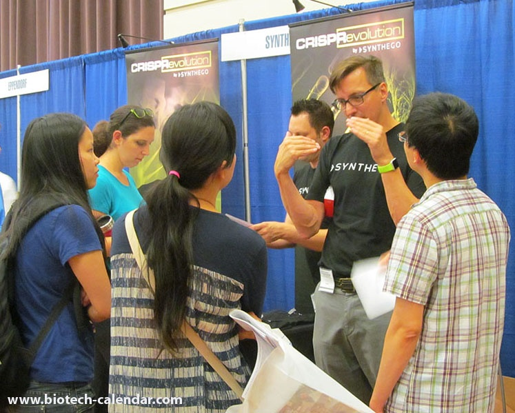 Lab product specialist explaining new equipment to researchers at last year's event