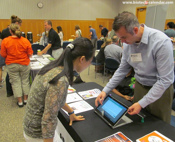 A vendor uses a tablet computer to display new events and laboratory products available at the BioResearch Product Faire™ at the University of Michigan.